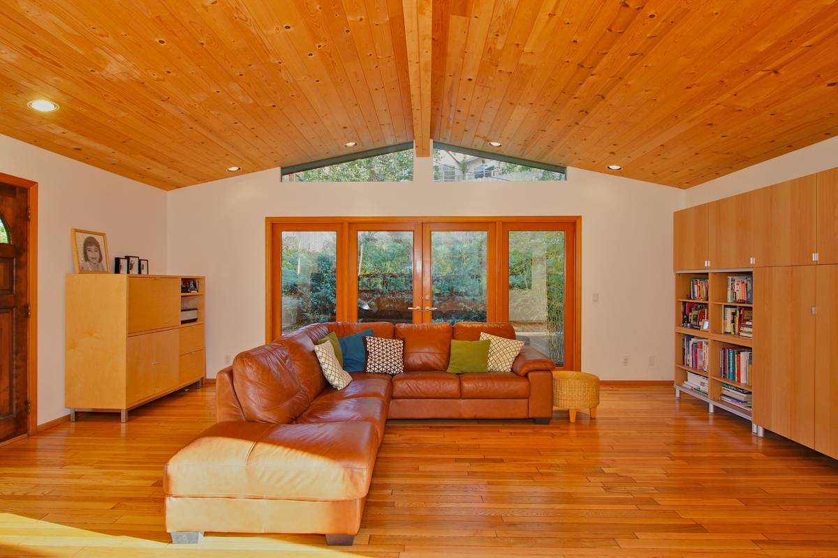 Living room with exposed center beam and pine ceilings.