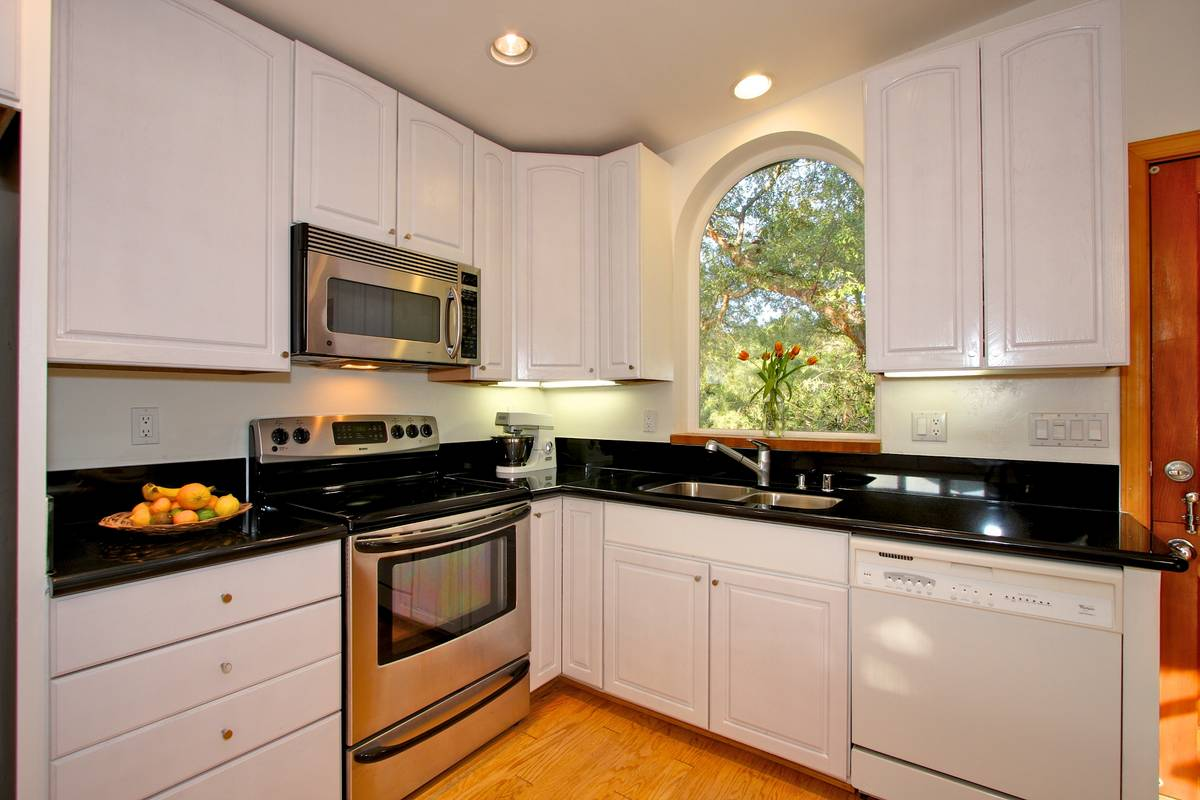 Beautiful kitchen with butcher block and granite counters.