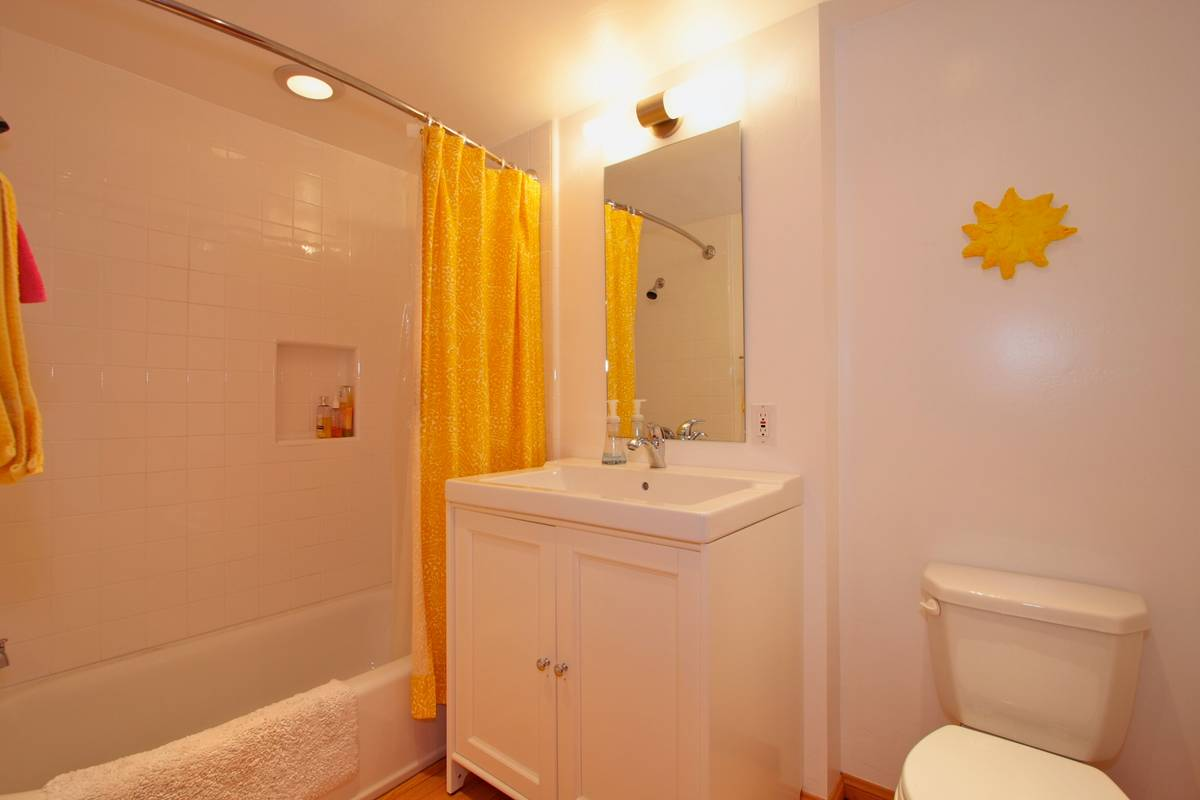 Cheery second bath features a shower/tub combo.