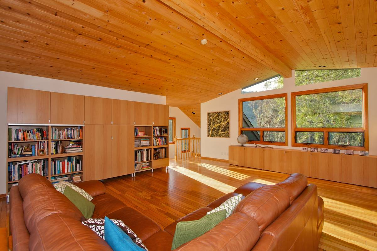 Spacious living room with hardwood floors and views of the hills.
